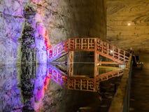 Belichtete Stalaktiten vom Salz und von der Holzbrücke über dem Reservoir in den Salzbergwerken in Slanic - Salina Slanic Prahova Lizenzfreies Stockfoto