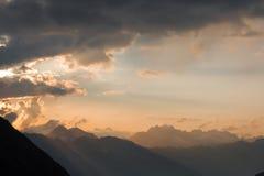 Belichtete Wolken in den Bergen mit Sonnenstrahlen shinin Lizenzfreie Stockfotos