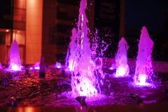 Belichteter farbiger Nachtbrunnen in der Stadt Stockbilder