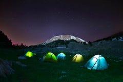 Belichtetes gelbes Campingzelt unter Sternen nachts Stockfotos