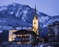 Belichtetes katholische Kirche St. Margaretha mit Straße, Lichtern, Bergen und Wald in Kaprun Österreich an der blauen Stunde stockfoto