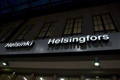 Belichtetes weißes Zeichen auf Dunkelheit mit den Buchstaben von Helsinki und von Helsingfors, Finnland Stockfoto