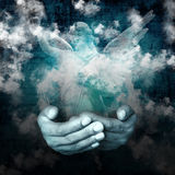 Belief. Hand holding an angel with cloud background