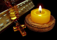 Belief candle. The macro bible photo with a gold sawn-off shotgun and an amber necklace with a cross and a burning candle Royalty Free Stock Photo