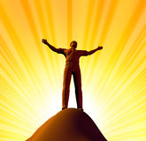 Belief and spirituality. Representing worship and the power of faith represented by a single man on the top of the mountain with his arms raised to god Royalty Free Stock Photos