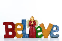 Believe. Letters spell out Believe with an Angel for the I on white background Royalty Free Stock Photo