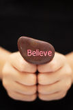 Believe. Hands holding a stone engraved with the word BELIEVE Stock Images