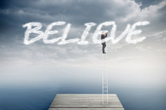 Believe against cloudy sky over ocean Royalty Free Stock Photography