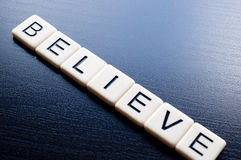 Believe on dark wood background Stock Images
