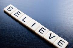 Believe on dark wood background Stock Images