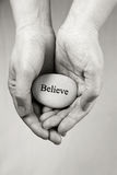 Believe. Hands holding a rock with engraved word Believe Royalty Free Stock Photos