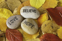 Believe, Love, Hope. Believe, love and hope message rocks with colorful fall leaves Royalty Free Stock Photos