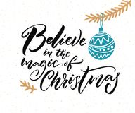 Believe in the magic of Christmas. Calligraphy caption for greeting cards and gift tags. Hand drawn illustration of Christmas tree branch with blue ball Stock Images