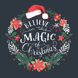 Believe in the Magic of Christmas wreath. Believe in the Magic of Christmas. Decorative wreath with hand drawn typography and Santa Claus hat Royalty Free Stock Photography
