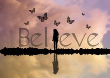 Believe scritto con la ragazza e le farfalle Fotografia Stock