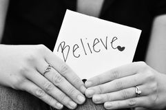 Believe sign. Being held in ladys hands in black and white format Stock Images