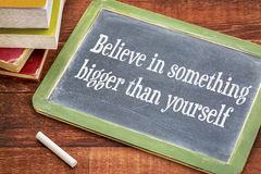 Believe in something bigger than yourself on blackboard. Believe in something bigger than yourself - inspirational phrase on a slate blackboard with a white stock photos