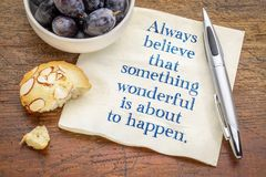 Always believe that something wonderful is about to happen. Handwriting on a napkin with grapes and cookie stock image