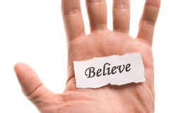 Believe word in hand. Word on piece tear paper Stock Images