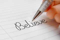 Believe word handwriting. Believe word concept background on paper Stock Image