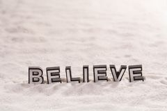 Believe word on white sand Royalty Free Stock Image
