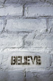 Believe word. Textured black stencil print of believe word on the grunge brick wall Royalty Free Stock Photo