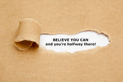 Believe you can and you are halfway there. The text Believe you can and you`re halfway there, appearing behind torn brown paper Stock Images