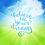 Believe in your dreams hand-drawn lettering. Over sunny summer background with clouds, vector illustration Stock Photography