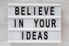 `Believe in your ideas` words on modern board over white wooden surface, top view. Flat lay, from above, overhead stock image