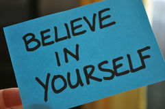 Believe In Yourself. A bright blue note with the words Believe In Yourself written on it in capital letters in black marker pen Stock Photography