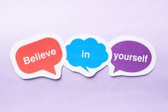 Believe in yourself. Concept paper bubbles against purple background Royalty Free Stock Photography
