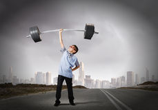 Believe in yourself. Cute boy of school age lifting barbell above head Stock Photos