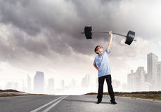 Believe in yourself. Cute boy of school age lifting barbell above head Royalty Free Stock Image