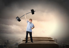 Believe in yourself. Cute boy of school age lifting barbell above head Royalty Free Stock Images