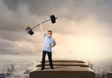 Believe in yourself. Cute boy of school age lifting barbell above head Stock Photography