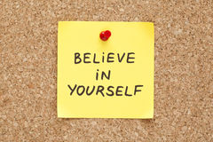 Sticky Believe In Yourself. Believe In Yourself, written on an yellow sticky note on a cork bulletin board Stock Photos