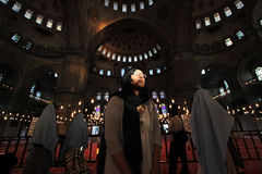 Believer in Blue Mosque Wide Angle. A woman in Blue Mosque (Sultanahmet) stands dramatically. A light comes onto her face. Shot with wide angle Royalty Free Stock Photo