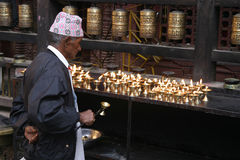 Believer in Golden Temple. Believer lighting a candle in Golden Temple in Patan, Nepal with a typical Nepalese cap Royalty Free Stock Photos