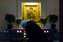 A believer lights a candle near the icons of St. Mary. Royalty Free Stock Photo