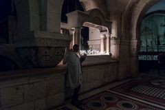 The believer reads a prayer by the book in Church of the Holy Sepulchre in the Old City of Jerusalem in Israel. Jerusalem, Israel, December 28, 2018 : The royalty free stock images