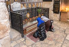 Believers kneel and pray in the lower hall in Alexander Nevsky church in Jerusalem, Israel. Jerusalem, Israel, November 17, 2018 : Believers kneel and pray in stock image