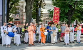 Believers of the Society for Krishna Consciousness in the center of Lviv in Ukraine, near the Opera House plays drums, harmonica. Believers of the Society for royalty free stock image