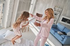 She always believes in her. Top view of cute little girl jumping. On the bed with her mother while spending time at home Stock Photo