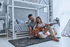 He always believes in her. Young father teaching his little daughter to play guitar and smiling while sitting on the floor in bedroom Stock Images