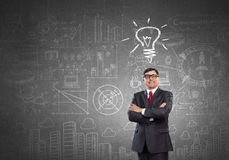 He believes in success. Experienced businessman in glasses standing with hands crossed on chest Stock Image