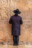 Believing pray near the wall of crying in a black hat. Believing pray near the wall of crying in a big black hat stock photo