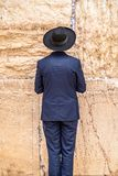 Believing pray near the wall of crying in a black hat. Believing pray near the wall of crying in a big black hat royalty free stock photography