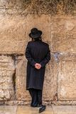 Believing pray near the wall of crying in a black hat. Believing pray near the wall of crying in a big black hat royalty free stock images
