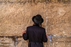 Believing pray near the wall of crying in a black hat. Believing pray near the wall of crying in a big black hat royalty free stock photo