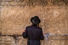 Believing pray near the wall of crying in a black hat. Believing pray near the wall of crying in a big black hat stock photos